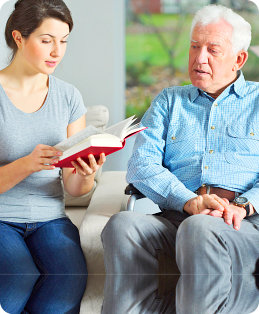 Senior care assistant reading book to elderly man