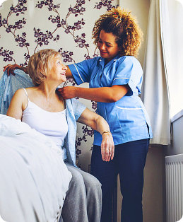 Home caregiver helping a senior woman get dressed in her bedroom