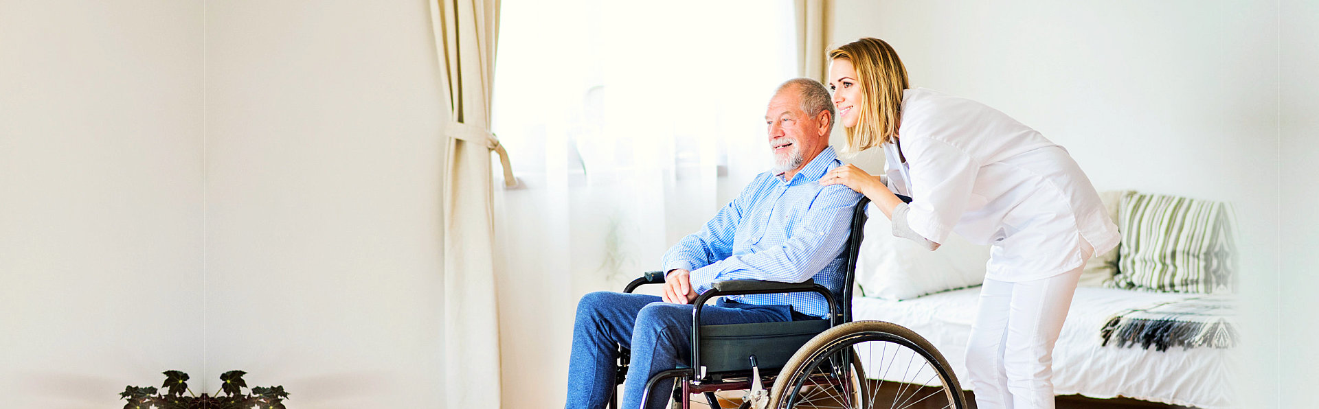 urse and senior man in wheelchair during home visit